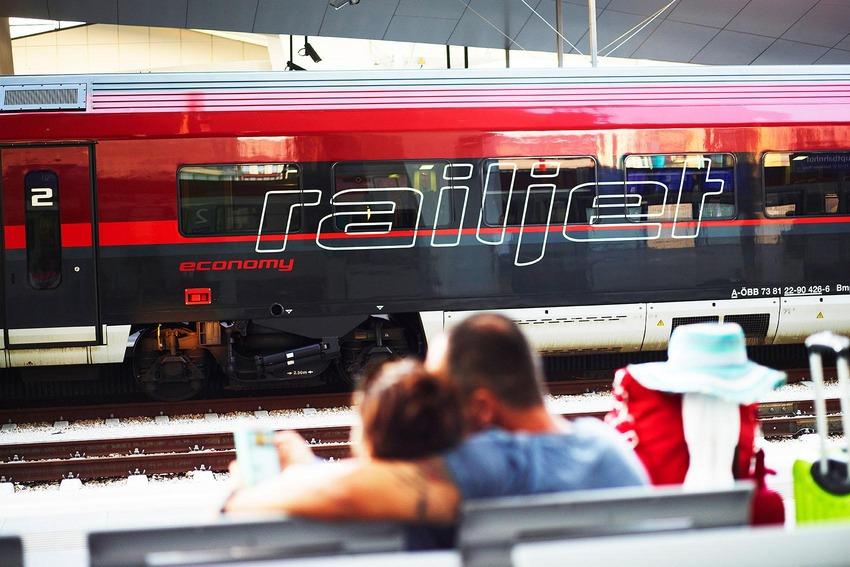 Paar sitzend um umarmend auf Bank, Hintergrund Railjet