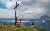 Familie unter Gipfelkreuz in der Region Kaiserwinkl