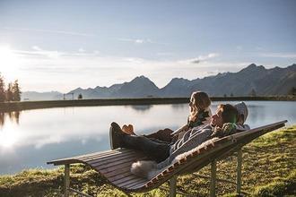 2 Wanderer relaxen vor einem Speichersee