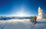 3 Skifahrer vor verschneiter Kapelle
