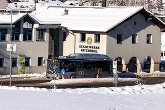 Elektro-Bus fährt durch winterliches Kitzbühel