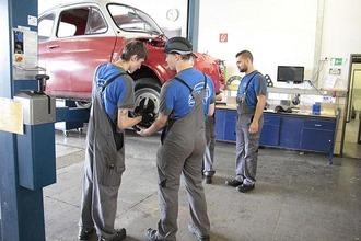 Lehrlinge und Postbus Mitarbeiter stehen in Werkstatt vor einem Oldtimer-Wagen