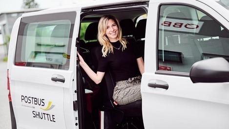 Frau steigt aus Postbus Shuttle