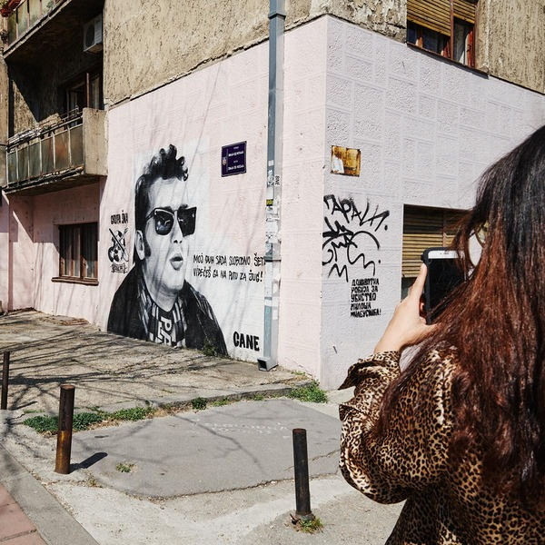Frau fotographiert ein Graffiti mit ihrem Smartphone