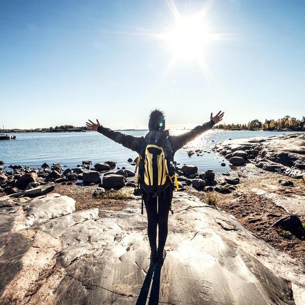 Frau steht mit ausgebreiteten Armen vor einem See