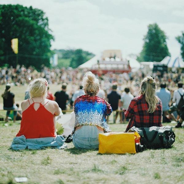 Leute sitzen auf einer Wiese und blicken auf eine Bühne