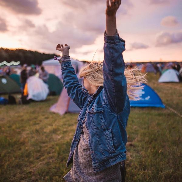 Eine Frau tanzt inmitten eines Campingplatzes