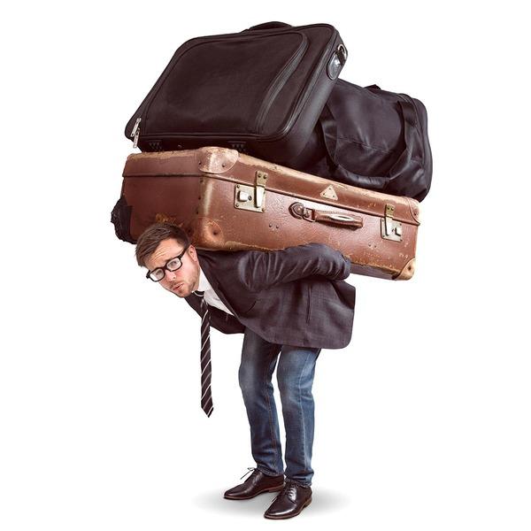Mann schleppt Koffer und Taschen auf seinem Rücken
