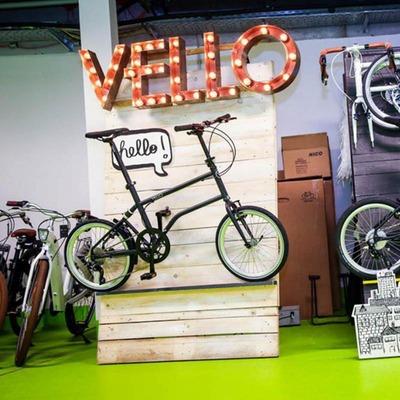 """Ein Fahrrad unter einem leuchtenden """"Vello"""" Schriftzug"""