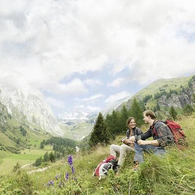 Ein Wandererpärchen sitzt auf einem Hügel im Gras