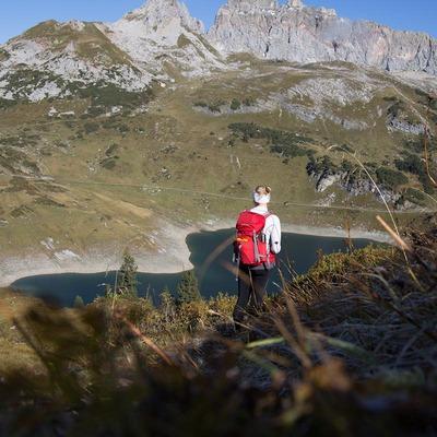 Eine Wanderin blickt auf einen See