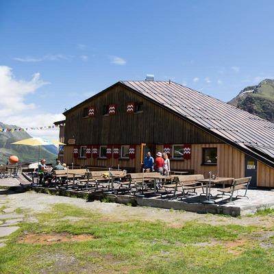 Eine große Holzhütte, davor stehen einige Tische und Stühle