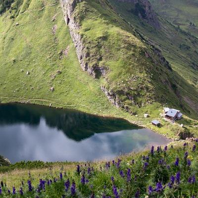 Eine wunderschöne Landschaftsaufnahme, in der Ferne sieht man ein Häuschen am See