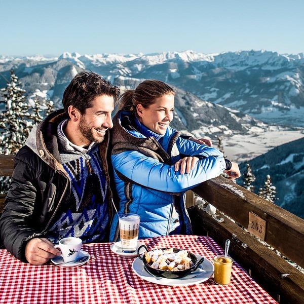 Pärchen sitzt auf einer Skihütte und genießt den Ausblick