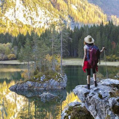 Eine Wanderin steht auf einem Felsen und blickt auf einen glasklaren See