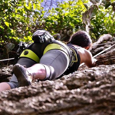 Frau beim gesicherten Klettern an einer Felswand