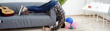 Schlafender Mann hängt kopfüber vom Sofa