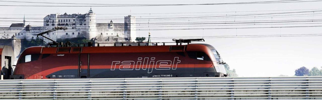 Ein Railjet fährt über eine Brücke, im Hintergrund sieht man die Festung Hohensalzburg