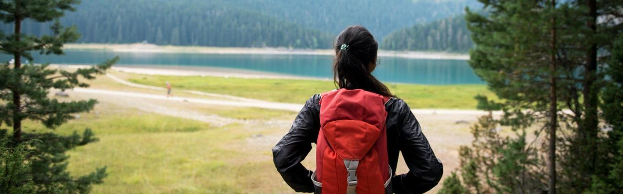 Frau mit Rucksack blickt auf eine Graslandschaft mit einem See in weiter Ferne