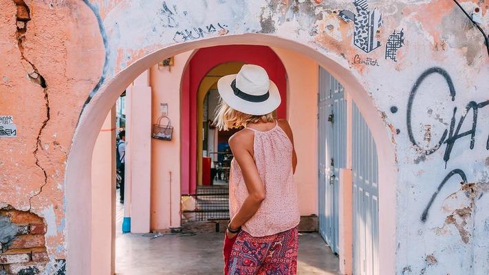 Frau durchschreitet einen Torbogen in einer Stadt