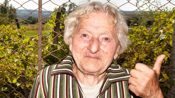 """Portrait-Foto einer alten Frau mit """"Dauen hoch"""" Geste"""
