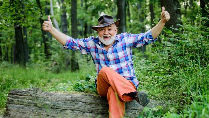Ein älterer Farmer sitzt im Wald und freut sich