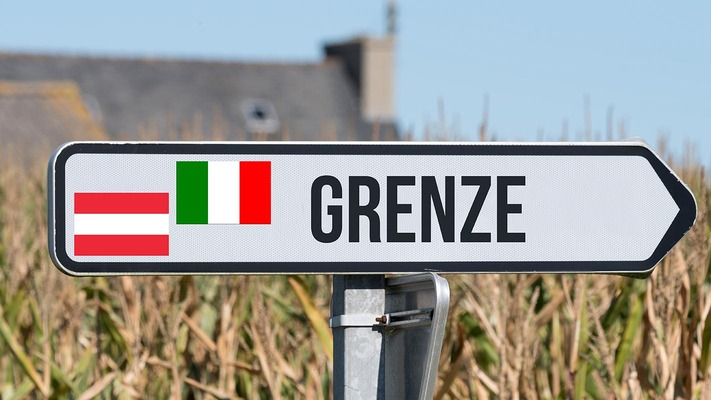 """Ein Wegweise mit der Aufschrift """"Grenze"""" und den Fahnen von Österreich und Italien"""