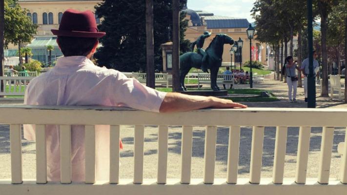 Mann sitzt auf Parkbank