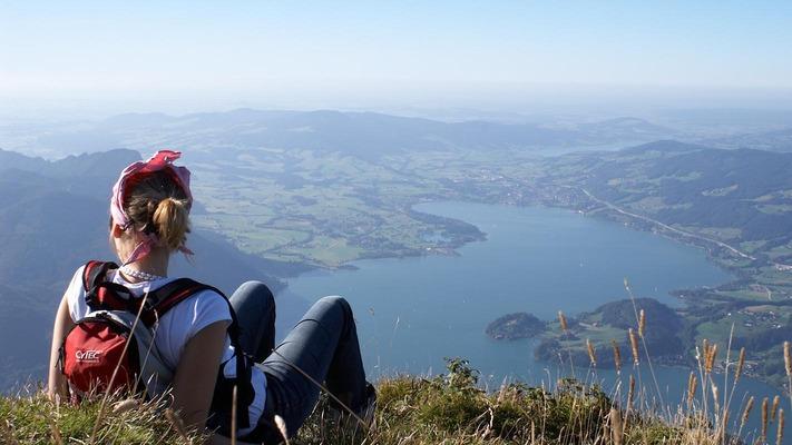 Frau mit Wanderrucksack sitzt auf Grashügel und blickt in die Ferne