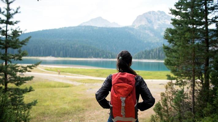 Frau mit Wanderrucksack blickt auf See