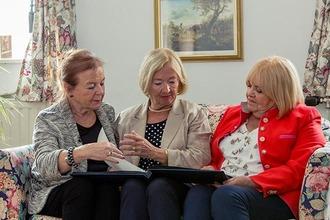 Die 3 Damen vom Gleis sitzen am Sofa und blättern durch ein Fotoalbum