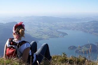 Wanderin sitzt auf Hügel und genießt den Ausblick