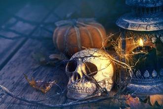 Totenkopf und Laterne vor düsterem Hintergrund