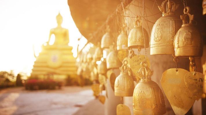 Kleine goldene Glocken vor einer buddhistischen Statue