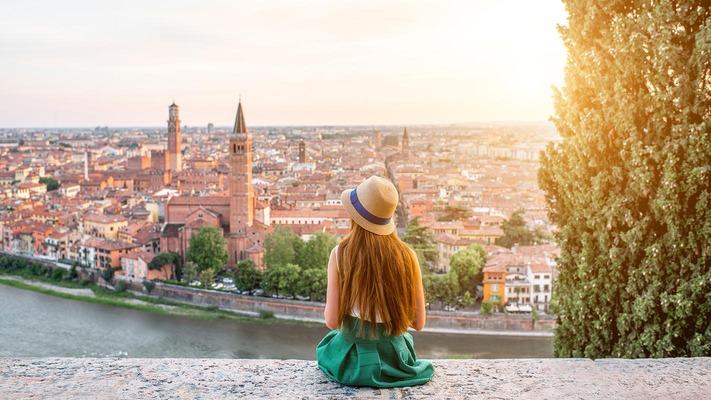Eine junge Frau blickt von einem Hügel auf Verona