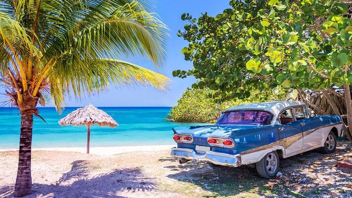Ein typisch kubanisches Auto steht am Sandstrand