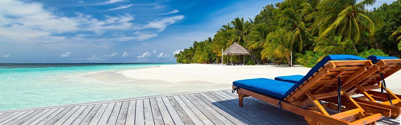 Strandliegen auf Holzsteg vor karibischer Kulisse