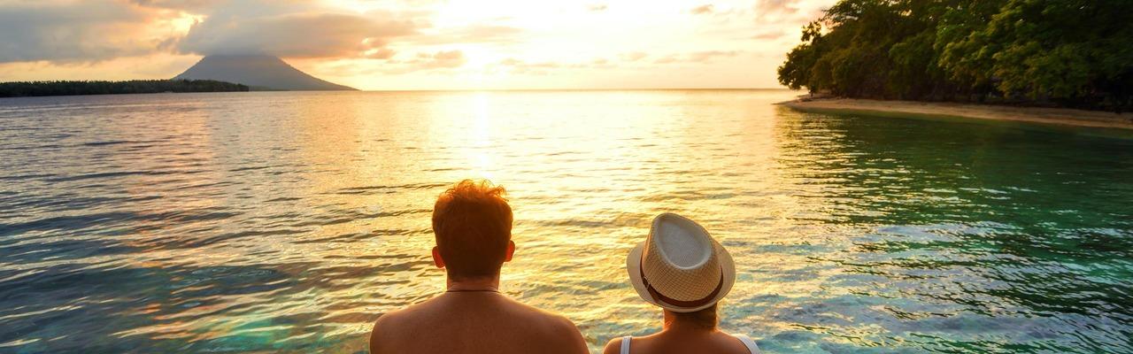 Ein Paar sitzt am Steg und blickt auf den Sonnuntergang am Meer