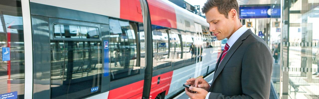 Businessreisender am Bahnsteig vor ÖBB Talent