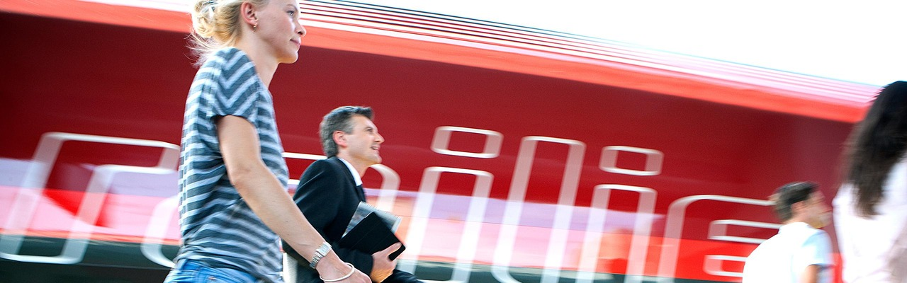 Pendler am Bahnsteig vor dem ÖBB Railjet