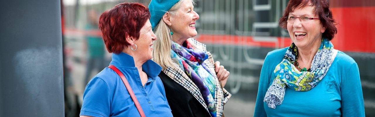 Three senior women on the platform in front of ÖBB Railjet