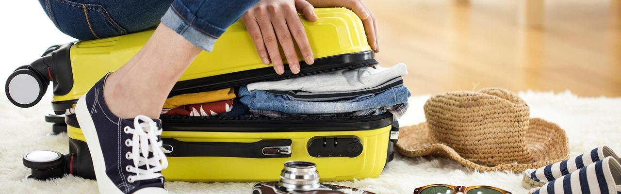 Frau kniet auf Koffer weil sie zuviel eingepackt hat