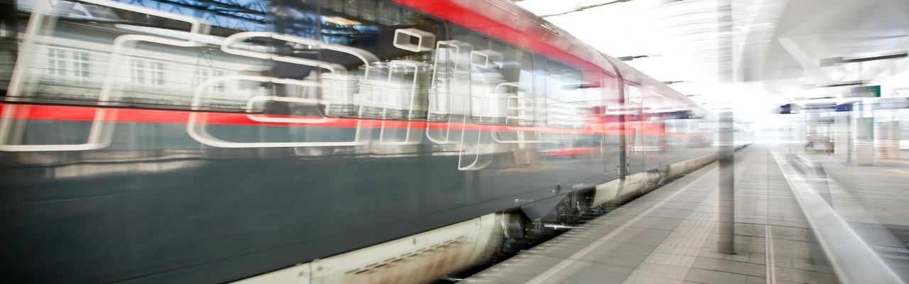 Railjet fährt durch Bahnhof