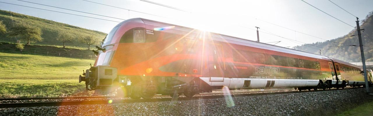 Railjet fährt durch Sonnenuntergang