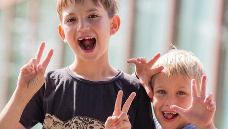 """Zwei Kinder zeigen das """"Peace"""" Zeichen mit ihren Händen"""
