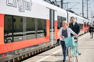 Frau mit Fahrrad am Bahnsteig