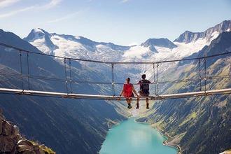 Ein junges Paar sitzt auf einer Hängebrücke und lässt die Füße in den Abgrund baumeln