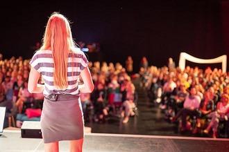 Frau auf Bühne vor Publikum