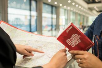 Frau hält Berlin-Card und eine Landkarte