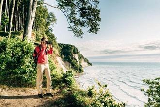 Mann mit Kamera steht vor Küstenregion